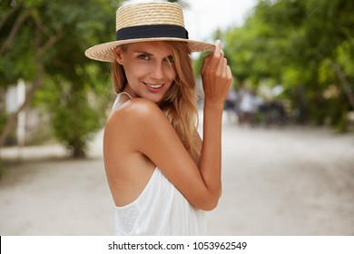 Outdoor shot of pleasant looking female with tanned healthy skin, dressed in white dress and summer hat, poses in park with confident satisfied expression, likes recreation. Beautiful young woman