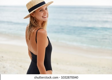 Outdoor shot of pleased female with sunburnt skin, wears straw hat and swimsuit, has walk across coastline, enjoys good rest at seaside, looks happily away at friends. People and summer vacations