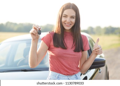 Outdoor shot of satisfied beautiful brunette female owner of car, likes and rejoices her purchase, holds keys and keeps thumb raised, has happy expression, stands near new automobile, going to drive