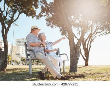 Outdoor shot of a senior couple sitting on a park bench with woman showing something interesting to her  husband. Retired couple taking a break and relaxing on a bench.