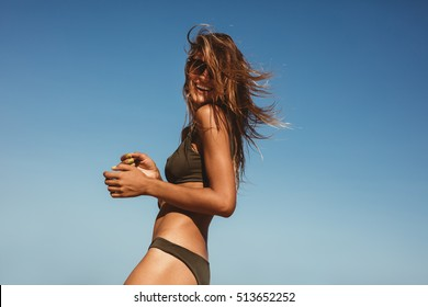 Outdoor shot of smiling young female model in bikini standing against blue sky. Woman having fun out on a summer day.