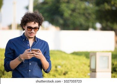 an outdoor shot a standing young man holding his phone and typing to his friends.