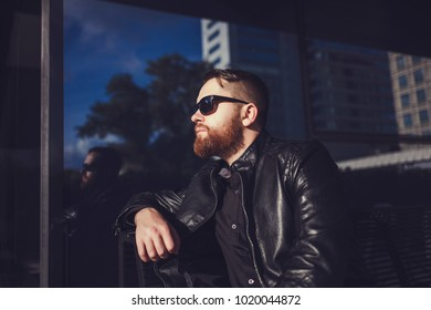 Outdoor shot of stylish young man wearing leather jacket sitting in urban surroundings