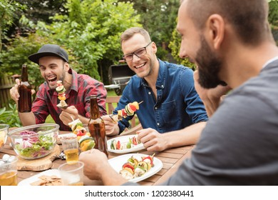 Outdoor shot of three friends enjoying barbecue party in garden, sitting at the table and eating vegetable skewers.