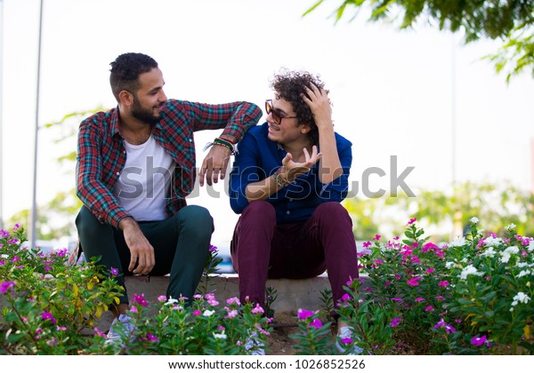an outdoor shot of two friends sitting on the sidewalk taking while sitting in a springy view between the flowers in a casual outfit.