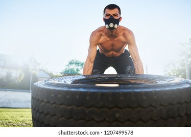Outdoor shot of young athlete male in mask to increase load on breathing muscles doing exercise with big tire outdoors in stadium on sunlight. Copy space. Shirtless sportsman doing workout, healthy