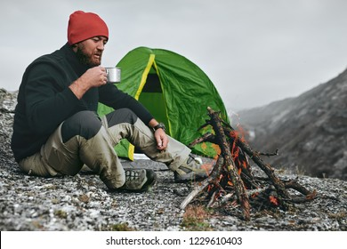 Outdoor shot of young breaded male drinking hot beverage in mountains. Traveler man in red hat, sitting near to camping tent, holding in hands a mug of tea after hiking. Travel, lifestyle.