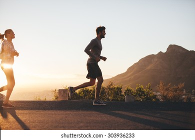 Outdoor shot of young couple on morning run. Young man and woman jogging on road outside during sunrise.