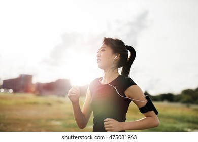 Outdoor shot of young fitness woman running in the park. Chinese female running exercising in morning.