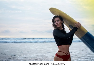 Outdoor shot of young girl waxes surfboard for safe riding waves, dressed in black swimsuit, takes care of safety, with white lines mask on her pretty face around eyes, enjoys freedom. Pastime concept