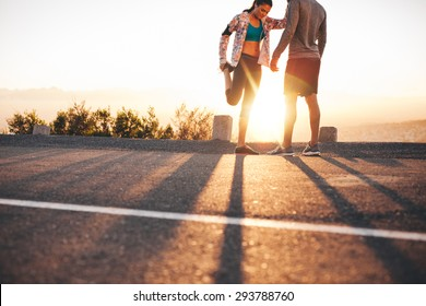 Outdoor shot of young joggers stretching before a run in morning. Young man standing and woman stretching her legs at sunrise.