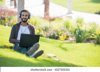 An outdoor shot of a young man sitting in the garden listening to music using his laptop, smiling.