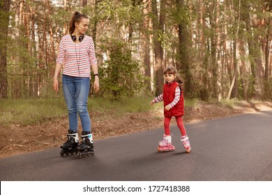 Outdoor shot of young mummy with her cute daughter rollerblading in forest on asphalt road, mom looking at her child, wearing casual outfits, family spending time together in open air. People concept