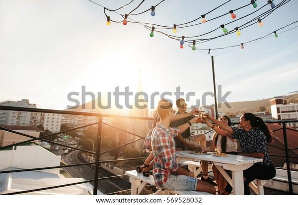 屋上のパーティーで飲み物を飲む若者のアウトドアショット。酒を飲みながら遊ぶ若い友達。