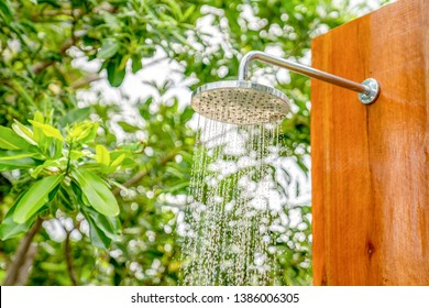Outdoor shower head stick on the wooden plate pole design for showering body before jumping in the resort pool.