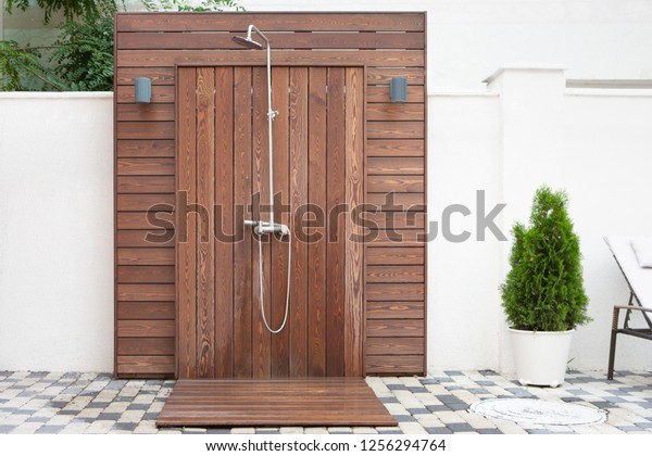Outdoor Shower Made From Brown Wood Near Swimming Pool.