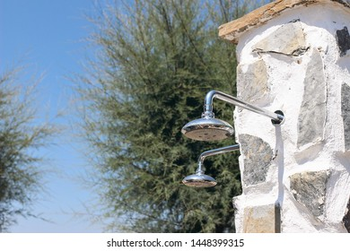 Outdoor shower sprinkler at the beach. Shower heads beside the pool. Cooling, refreshment concept at hot summer day. Blue sky with blurred trees background. Selective focus.