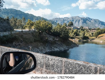 Outdoor and side mirror view from car window. Ponte Nova bridge and Cavado river in Geres National Park.