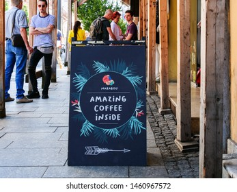 Outdoor sidewalk sign inviting people to a coffee in a building under restoration in Cluj-Napoca, Romania on July 16, 2019.