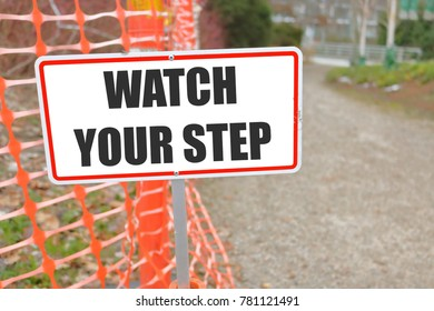 An outdoor sign in a construction zone warns pedestrians to watch their step while in the area.