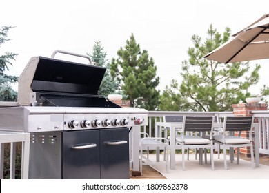 Outdoor six-burner gas grill on the back patio of a luxury single-family home.