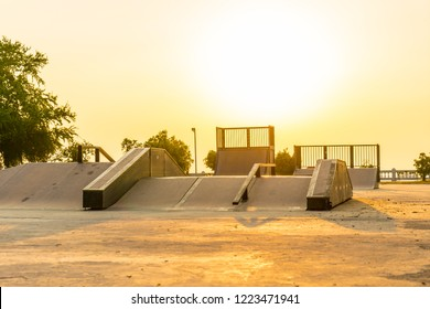 Outdoor skatepark with various ramps on sunset time