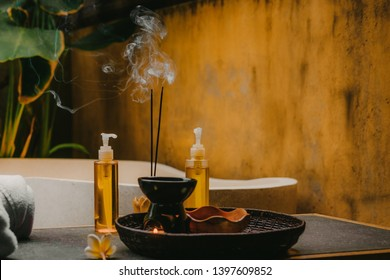 Outdoor spa salon. Massage oils, burning incense sticks with smoke, towels, flowers on wooden  stone table. Bath, green leaves on background
