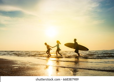 Outdoor sport activity friendship concept : Silhouette of group of young joyful surfer friend running into the sea with surf boards on sunset beach