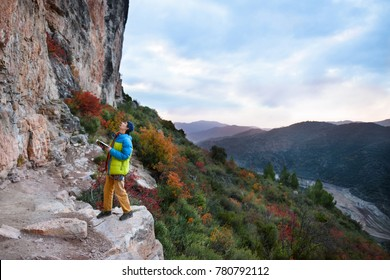 Outdoor sport activity. Rock climber choosing a sport climbing route a challenging cliff. Travel destination, Spain, Europe.