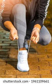Outdoor Sport Concepts. Active Female Runner Tighten Up Her Shoelaces During Jogging Training Exercise Outdoor. Vertical Image