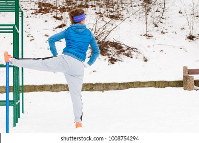 Outdoor sport exercises, sporty outfit ideas. Woman wearing warm sportswear urban street training exercising outside during winter.