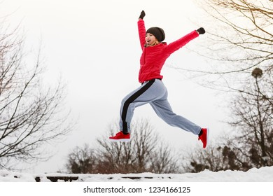 Outdoor sport exercises, sporty outfit ideas. Woman wearing warm sportswear training exercising outside during winter, jumping out of joy.