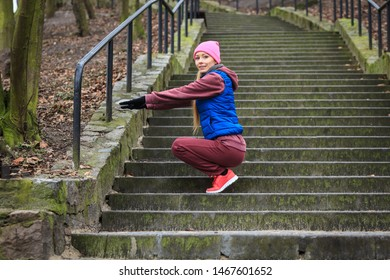 Outdoor sport exercises, sporty outfit ideas. Woman wearing warm sportswear training exercising outside during autumn, warming up before workout.