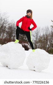Outdoor sport exercises, sporty outfit ideas. Woman wearing warm sportswear training exercising outside during winter. Having fun while making snowman