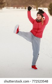 Outdoor sport exercises, sporty outfit ideas. Woman wearing warm sportswear training exercising stretching legs outside during winter.