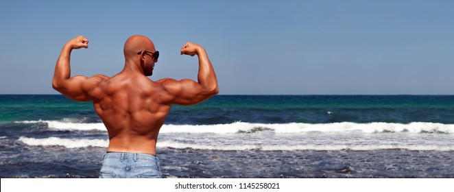 Outdoor sport and healthy lifestyle banner.  Italian bodybuilder posing with flexing arms to show biceps and shoulder against the blue sea and sky.  Wide panorama