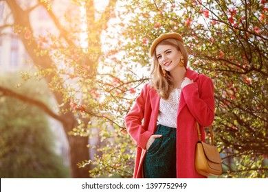 Outdoor spring fashion portrait of young beautiful happy smiling lady wearing trendy coral color coat, carrying yellow shoulder bag, posing in park with blooming trees. Copy, empty space for text