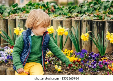 Outdoor spring portrait of a cute little boy playing in the park on a nice sunny day, wearing colorful clothes