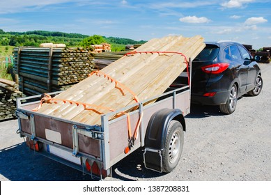 Outdoor stacking the logs on utility trailer for transport at sawmill in europe with background green forest ,blue sky and clouds. industrial wood yard with stacks of new wood poles.