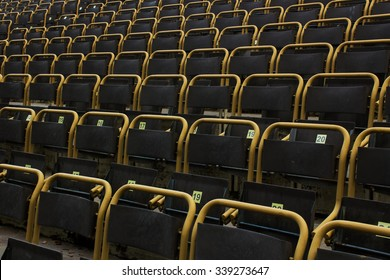 Outdoor stadium dark seats with yellow frames with visible one point perspective from a side