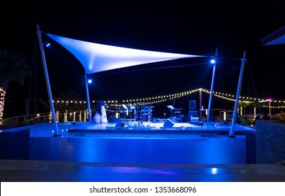 outdoor stage music on the beach by the sea at night .