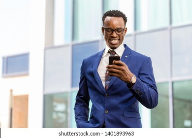 Outdoor standing portrait of a black African American business man using a mobile  phone