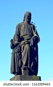 An outdoor statue of St Joseph with a young Christ, on the Charles Bridge, Prague. He holds a flowering rod. The sky behind is blue.