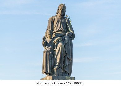 An outdoor statue of St Joseph with a young Christ, on the Charles Bridge, Prague. He holds a flowering rod. The sky behind is blue