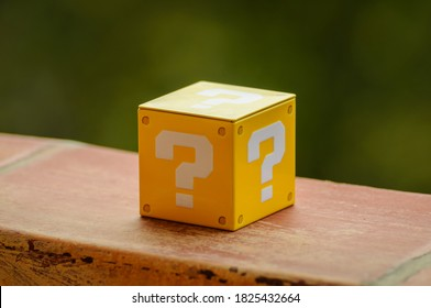 Outdoor still-life photo of a yellow box with a big white question mark printed on each face. It recalls a graphic element of a famous platform video game. Cube lighted from the right side.