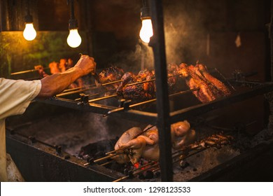 outdoor street chicken barbecue grill arm and hand brush oiling the grilling meat food broiler spit roasted over smoking living coals in a simple electric illumination, the Philippine lechon Manok