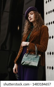 Outdoor street fashion portrait of young lady wearing stylish autumn outfit: brown corduroy blazer, purple beret, culottes, holding trendy textured snakeskin green handbag