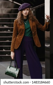 Outdoor street fashion portrait of young curly woman wearing stylish autumn outfit: brown corduroy blazer, green turtleneck, purple beret, culottes, holding trendy textured snakeskin handbag