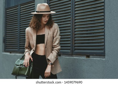 Outdoor street style fashion portrait of  elegant woman wearing beige hat, blazer, black crop top, high-waisted trousers, holding green leather handbag, posing in street of the city. Copy, empty space