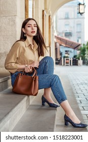 Outdoor, street style, fashion portrait of elegant, fashionable woman wearing beige shirt, blue jeans, wrist watch, snakeskin, python print, textured shoes, holding brown bag, posing in European city